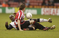 Photo: Aidan Ellis.<br /> Sheffield United v Swansea City. The FA Cup. 06/01/2007.<br /> Swansea's Adebayo Akinfenwa keeps an eye on the ball in a challenge with Sheffield's leigh Bromby