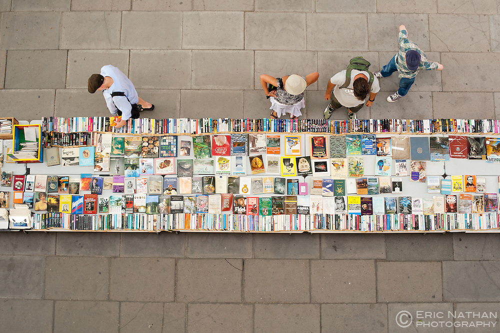 People browsing second hand books on the South Bank of the Thames in London.
