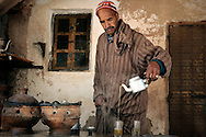 Morocco, High Atlas Mountains. Berber man pouring the a la menthe to small glasses.