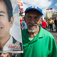 An elederly man joined large crowds and demonstrated against Juan Orlando Hernández and electoral fraud. He holds a banner with the face of the candidate Salvador Nasralla.