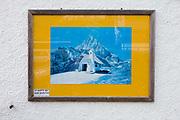 Detail of a framed picture of a Dolomites mountain hut, on sale in a  tourist shop selling tourist memorablia on Passo Falzarega (Pass) in south Tyrol, Italy. With just half a million inhabitants, south Tyrol attracts nearly 6m holidaymakers annually who total 29m overnight stays a year. The Dolomites are a mountain range in northeastern Italy and in August 2009, the Dolomites were declared a UNESCO World Heritage Site.