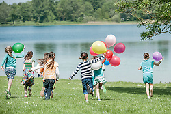 Rear view of children running in park with balloons, Munich, Bavaria, Germany