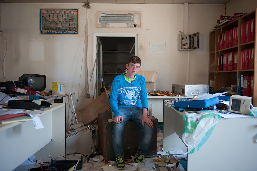 18 year old Adnan from Syria inside the office of an abandoned logistics company near Kara Tepe camp. Since the camp is overcrowded with appalling conditions many refugees decide to stay outside of it.