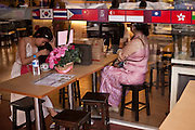 Two woman wait in a restaurant, Yangon, Burma.<br /> Note: These images are not distributed or sold in Portugal