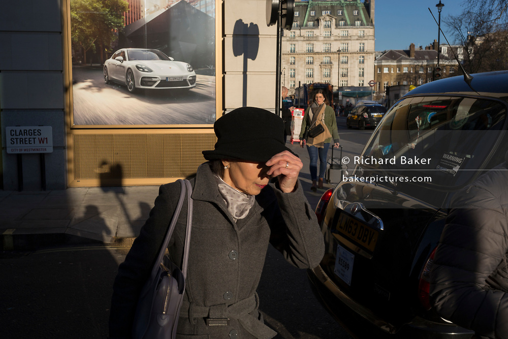 A lady shades here eyes from low, winter sunshine while walking past a Porsche luxury car ad where a new dealership is due to open on the corner of Clarges Street, and Piccadilly, W1, on 20th January 2020, in London, England.