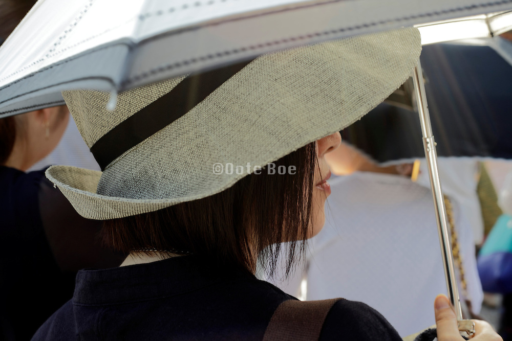 woman with large hat and umbrella to protect herself against the strong sun