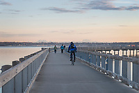 Bicyclist and two adult females on Boulevard Park Boardwalk, Taylor Dock on Bellingham Bay, Bellingham Washington