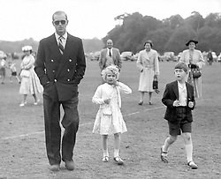 Princess Anne (c) adjusts her cardigan while her brother, Prince Charles, glances across at the Duke of Edinburgh at Smith's Lawn, Windsor Great Park, where they were watching the Polo.