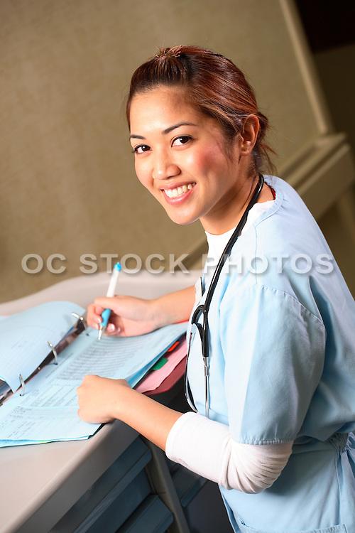Female Nurse Recording Patient Information