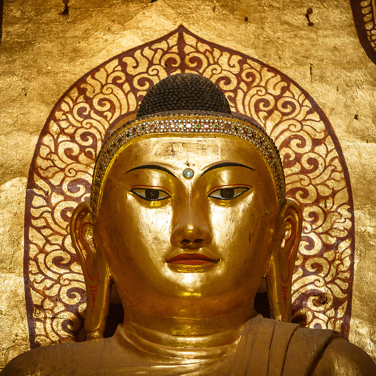"""Face of Buddha, Ananda Pahto, Bagan built in 1105 AD during the reign (1084–1113) of King Kyanzittha of the Pagan Dynasty. The temple layout is in a cruciform with several terraces leading to a small pagoda at the top covered by an umbrella known as hti, which is the name of the umbrella or top ornament found in almost all pagodas in Myanmar. The Buddhist temple houses four standing Buddhas, each one facing the cardinal direction of East, North, West and South. The temple is said to be an architectural wonder in a fusion of Mon and adopted Indian style of architecture. The impressive temple has also been titled the """"Westminster Abbey of Burma"""". The temple has close similarity to the Pathothamya temple of the 10th–11th century, and is also known as """"veritable museum of stones""""."""