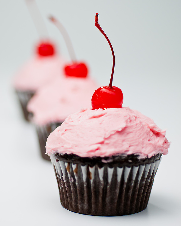 Home made chocolate cupcakes with pink frosting and a cherry on top. Portfolio photo  food photography for Carole Jones Commercial Photography