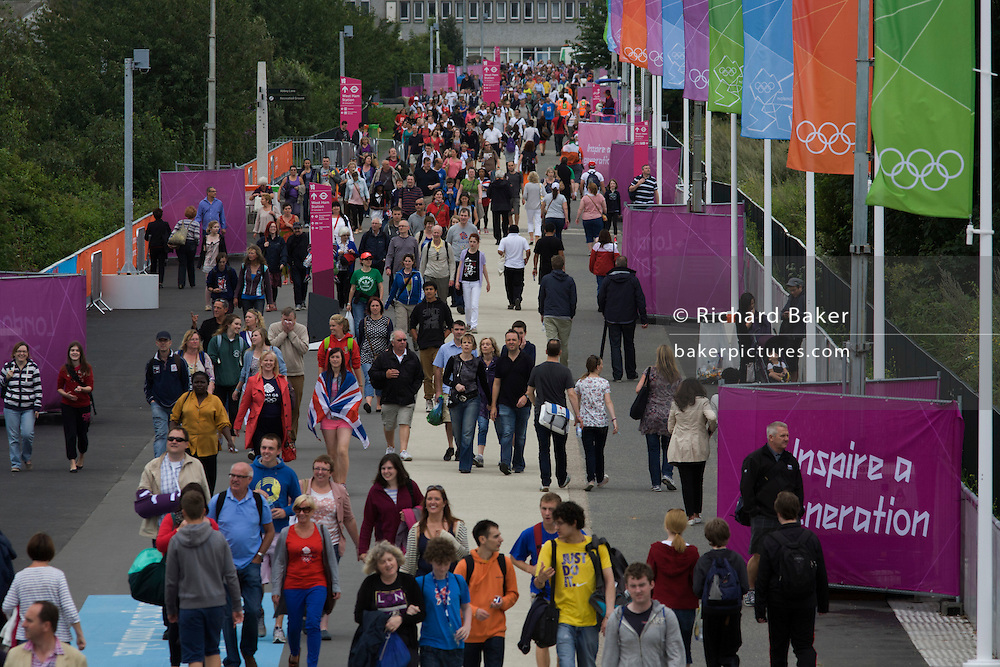 Aerial view of spectator crowds arriving across a newly-built walkway leading to the Olympic Park during the London 2012 Olympics, the 30th Olympiad. Approaching from the south, the sports fans approach the main Olympic Park, the location of eight venues including the main arena, Aquatics Centre and Velodrome plus the athletes' Olympic Village. After the Olympics, the park is to be known as Queen Elizabeth Olympic Park. .