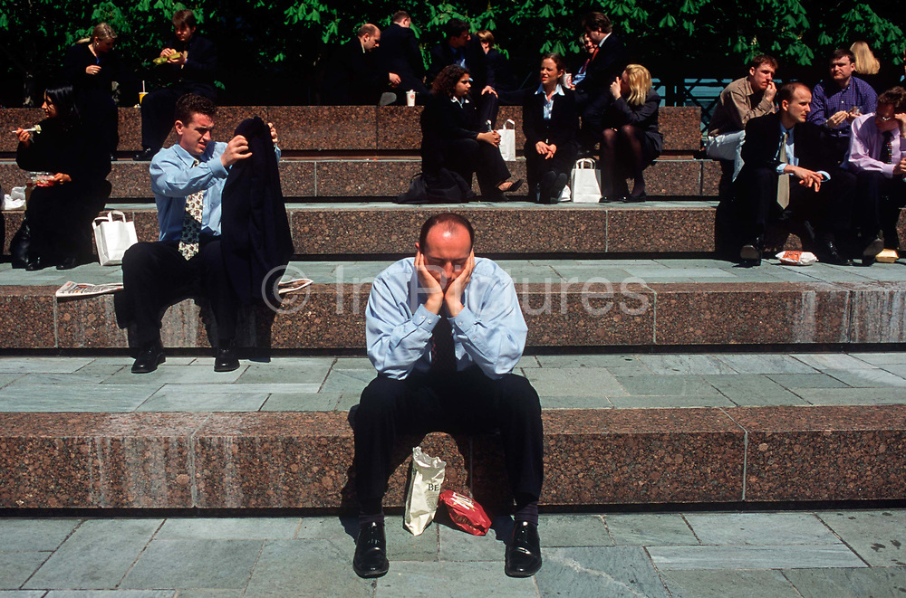 A 1990s tired office worker has forty winks at lunchtime in Broadgate in the City of London aka The Square Mile, the capitals financial centre, on 20th June 1993, in London, England.