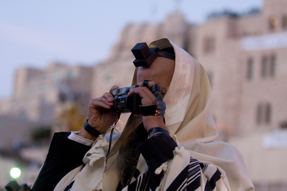 An ultra orthodox Jewish man wearing his prayer shawl and phylacteries, snaps a photograph using his old camera at the Western Wall, Judaism's holiest site during a mass prayer, on April 8, 2009.