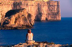 MALTA GOZO DWEJRA JUL00 - A Maltese fisherman sits atop the window of Dwejra.. . jre/Photo by Jiri Rezac. . © Jiri Rezac 2000. . Tel:   +44 (0) 7050 110 417. Email: info@jirirezac.com. Web:   www.jirirezac.com