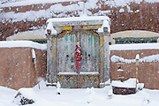 Snow-covered door with chili ristra