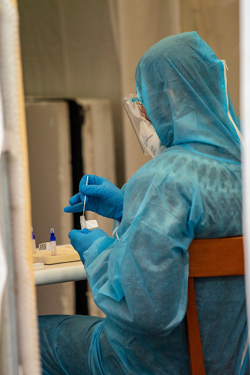 Medical personnel staff member processes a covid antigen rapid swab tests at a covid-19 test station outside the Kitkat night club in Berlin, Germany, December 13, 2020. Berlin's world famous KitKatClub has initiated a fast covid-19 tests operation in its premises People are able to set an online appointment and arrive to have a covid antigen rapid test swab test in what was reported by local media outlet as the lowest price in the German capital. The club itself is closed since early 2020 due to the health restrictions imposed on cultural venues in Germany.