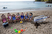A giant message in a bottle has washed up on the beach from countries ravaged by climate change, but the G7 leaders are too busy relaxing in their swimming costumes in deck chairs to notice, Oxfam campaigners pose as G7 leaders on a beach on the 12th of June 2021 near Falmouth, Cornwall, United Kingdom. Oxfam is calling on the G7 countries to commit to cutting emissions further and faster and provide more finance to help the most vulnerable countries respond to the impacts of climate change.