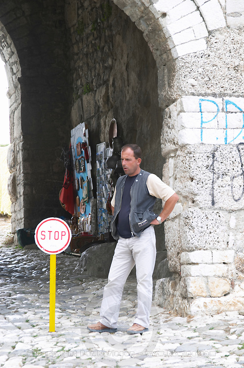 The entrance to the old city, arched gate in the stone wall, stop sign and a man ticket controller standing guard. Berat upper citadel old walled city. Albania, Balkan, Europe.