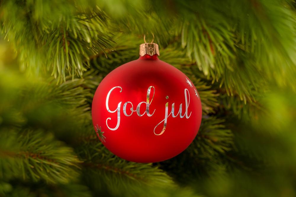 Rød julekule med sølvfarget norsk/svensk tekst «God jul» opphengt i juletre.