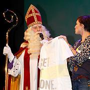 NLD/Amsterdam/20111117 - Inloop Bennie Stout in premiere voor Sinterklaas, Vivienne van den Assem  overhandigt een t-shirt van de stichting Get It Done
