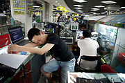Computer seller sleeping inside e-plaza digital square shopping mall. Zhongguancun or Zhong Guan Cun, is a technology hub in Haidian District, Beijing, China. It is situated in the northwestern part of Beijing city. Zhongguancun is very well known in China, and is often referred to as China's Silicon Valley. This is Beijing's computer district with numerous tech companies offices situated here amongst the many malls which sell electronics and electrons equipment of all kinds. The tech park started as a small office where two decades ago some students from a nearby university decided that computer equipment may be a thing of the future so set up a small company. It has expanded in this time to  cover many square kilometres.