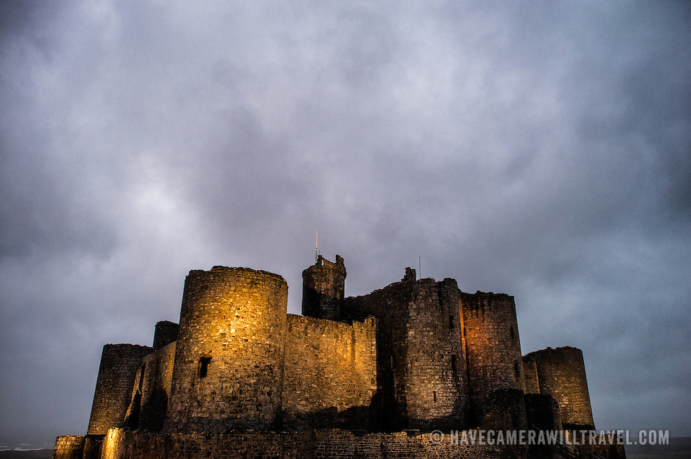 Dark skies and lights at Harlech Castle in Harlech, Gwynedd, on the northwest coast of Wales next to the Irish Sea. The castle was built by Edward I in the closing decades of the 13th century as one of several castles designed to consolidate his conquest of Wales.