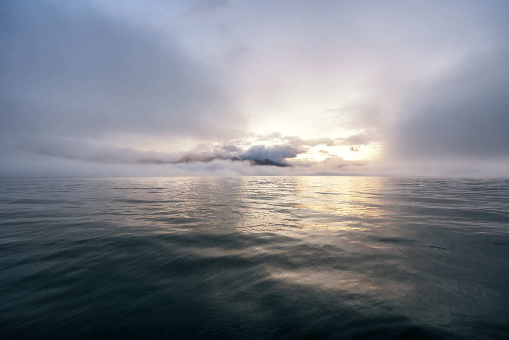 Morning light breaks through foggy skies as a swell rolls across the waters of Glacier Bay, Alaska