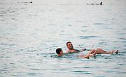 Israel, Dead Sea People float in the heavy water of the Dead Sea.