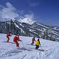 "SKIING, Big Sky, Montana.  Friends ski ""Ambush"" run with Lone Mountain in background. (MR)"