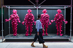 "© Licensed to London News Pictures. 28/07/2020. CITY, UK.  A staff member walks by costumes for the live visuals for ""Got to Keep On"", 2019, by The Chemical Brothers. Preview of ""Electronic: From Kraftwerk to The Chemical Brothers"" at the Design Museum in Kensington which is reopening after coronavirus lockdown.  The new exhibition explores the hypnotic world of electronic music, from its origins to its futuristic dreams.  The show runs 31 July 2020 – 14 February 2021 with visitors required to adhere to strict social distancing guidelines.  Photo credit: Stephen Chung/LNP"