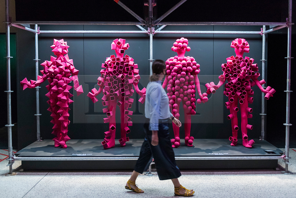 """© Licensed to London News Pictures. 28/07/2020. CITY, UK.  A staff member walks by costumes for the live visuals for """"Got to Keep On"""", 2019, by The Chemical Brothers. Preview of """"Electronic: From Kraftwerk to The Chemical Brothers"""" at the Design Museum in Kensington which is reopening after coronavirus lockdown.  The new exhibition explores the hypnotic world of electronic music, from its origins to its futuristic dreams.  The show runs 31 July 2020 – 14 February 2021 with visitors required to adhere to strict social distancing guidelines.  Photo credit: Stephen Chung/LNP"""