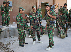 © Licensed to London News Pictures. 30/06/2014. Khanaqin, UK  Khanaqin, Iraq. Kurdish peshmerga fighters prepare to head out and relieve troops at the front line in Jalawla at a Kurdish peshmerga base in Khanaqin, Iraq. Counted by Kurds as part of their homeland, fighting in the town of Jalawla now consists of occasional skirmishes and exchanges of fire between snipers and heavy machine guns on both sides.<br /> <br /> <br /> The peshmerga, roughly translated as those who fight, is at present engaged in fighting ISIS all along the borders of the relatively safe semi-automatous province of Iraqi-Kurdistan. Though a well organised and experienced fighting force they are currently facing ISIS insurgents armed with superior armament taken from the Iraqi Army after they retreated on several fronts. Photo credit : Matt Cetti-Roberts/LNP