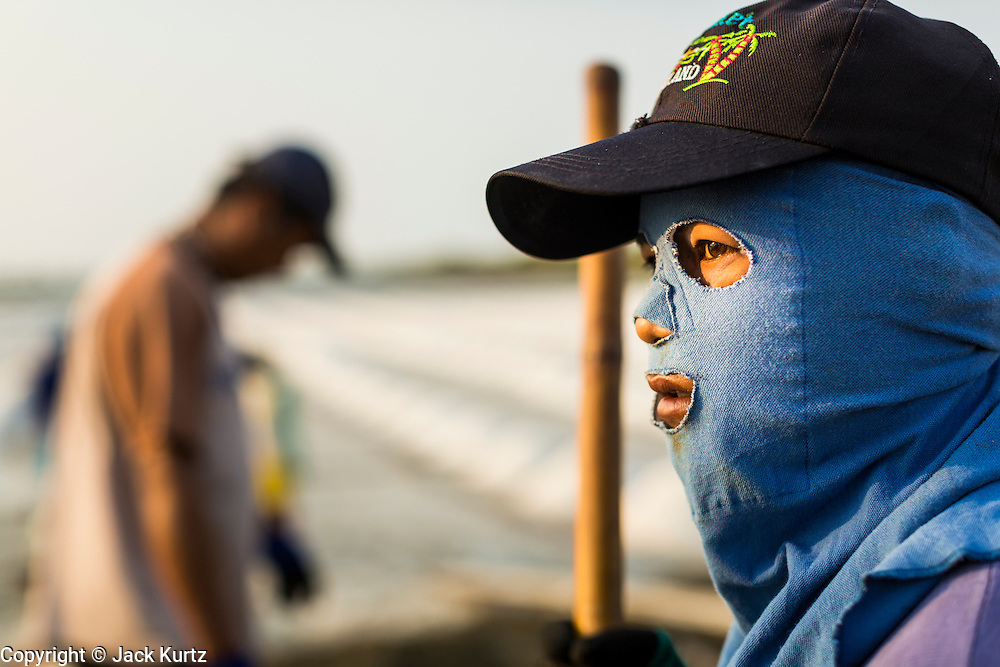 """28 MARCH 2014 - NA KHOK, SAMUT SAKHON, THAILAND: A salt worker near an evaporation pond in Samut Sakon province. Workers cover their bodies to protect them from the sun and briney water they stand in all day. Thai salt farmers south of Bangkok are experiencing a better than usual year this year because of the drought gripping Thailand. Some salt farmers say they could get an extra month of salt collection out of their fields because it has rained so little through the current dry season. Salt is normally collected from late February through May. Fields are flooded with sea water and salt is collected as the water evaporates. Last year, the salt season was shortened by more than a month because of unseasonable rains. The Thai government has warned farmers and consumers that 2014 may be a record dry year because an expected """"El Nino"""" weather pattern will block rain in mainland Southeast Asia. Salt has traditionally been harvested in tidal basins along the coast southwest of Bangkok but industrial development in the area has reduced the amount of land available for commercial salt production and now salt is mainly harvested in a small parts of Samut Songkhram and Samut Sakhon provinces.    PHOTO BY JACK KURTZ"""