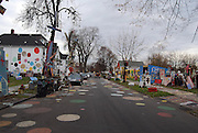 "The Heidelberg Project: Bringing Colour, Art, and Controversy to a Decaying Part of Detroit<br /> <br /> Watching the deterioration of his impoverished, crime-ridden neighborhood of McDougall-Hall two decades after Detroit's 1967 race riots, artist Tyree Guyton felt the need to do something. So he picked up a paintbrush and painted pastel polka dots all over his grandfather's Heidelberg Street house.<br /> Guyton's paint job was the first act toward what became the Heidelberg Project, an outdoor community art project aimed at breathing life back into his decaying district. Encouraged by his grandfather, and with the help of local kids, Guyton began decorating the abandoned homes beside the polka-dot house and installing art made from salvaged materials.<br /> The project now spans two blocks and is constantly evolving, anchored by the altered houses. One ramshackle two-story home is covered in stuffed animals. Another is painted with numbers of wildly varying sizes and colors. Strewn across the yards are sculptures incorporating decorated cars, shopping carts, doors, shoes, and household appliances.<br /> Though the infusion of color and creativity has attracted a stream of appreciative visitors to McDougall-Hall, the Heidelberg Project has some vocal critics. Chief among them is the city of Detroit, which demolished parts of the community in 1991 and 1999.<br /> Local detractors view the Heidelberg Project as an eyesore and health hazard, and resent the fact that it draws further attention to Detroit's urban blight. On November 12 of this year, the project's ""House of Soul,"" an abandoned house decorated with hundreds of records, burned to the ground in a suspected arson attack. This followed a suspicious fire in May, in which an art-enhanced building called the ""Obstruction of Justice House"" was destroyed.<br /> Undeterred, Guyton has responded to the destruction with relentless optimism and vowed to continue expanding his vibrant art community.<br /> <br /> *Visit Atlas Obscura for more on the Heidelberg Project.<br /> ©"