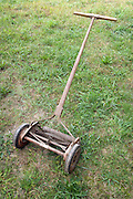 old lawnmower on an rough grass lawn