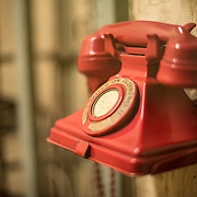 A red telephone at the Churchill War Rooms in London. The museum, one of five branches of the Imerial War Museums, preserves the World War II underground command bunker used by British Prime Minister Winston Churchill. Its cramped quarters were constructed from a converting a storage basement in the Treasury Building in Whitehall, London. Being underground, and under an unusually sturdy building, the Cabinet War Rooms were afforded some protection from the bombs falling above during the Blitz.