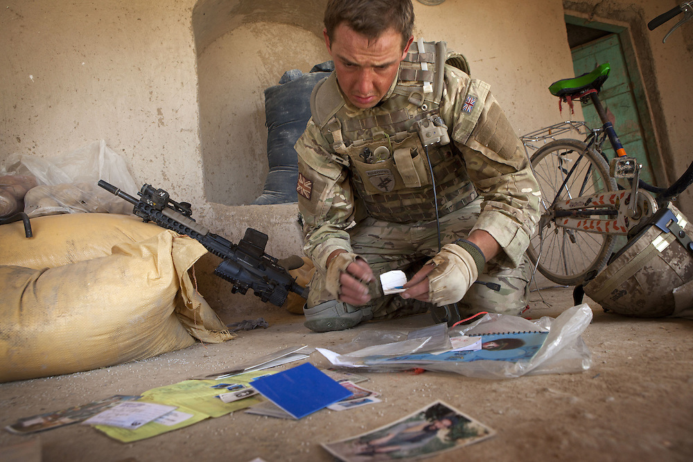 A British soldier of 16 Air Assault Bde's elite BRF (Brigade Reconnaissance Force) examines paperwork and photographs found whilst searching a compound as part of an operation in the village of Kakaran in Helmand Province, Southern Afghanistan on the 14th of March 2011.