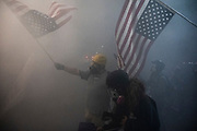 A demonstrator waves an upside down American flag as tear gas surrounds him at the Mark O. Hatfield United States Courthouse in Portland, Ore. on Saturday, July 25, 2020.
