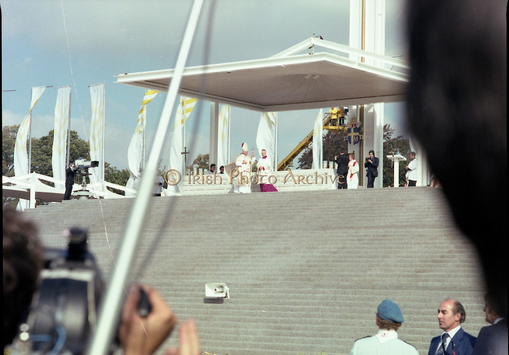 Pope John-Paul II visits Ireland..1979..29.09.1979..09.29.1979..29th September 1979..Today marked the historic arrival of Pope John-Paul II to Ireland. He is here on a three day visit to the country with a packed itinerary. He will celebrate mass today at a specially built altar in the Phoenix Park in Dublin. From Dublin he will travel to Drogheda by cavalcade. On the 30th he will host a youth rally in Galway and on the 1st Oct he will host a mass in Limerick prior to his departure from Shannon Airport to the U.S..Photograph of Pope John-Paul II as he stands to view the crowd from the altar.