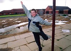 Boy playing near the shops on run down council housing estate; Bradford Yorkshire