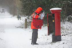 © Licensed to London News Pictures 08/02/2021.        Sevenoaks, UK. A postman collecting mail from a postbox in Chelsfield, Kent. The Met Office has warned of more freezing cold snowy weather to come with yellow and amber alerts in place for London, Kent and the South East. Photo credit:Grant Falvey/LNP