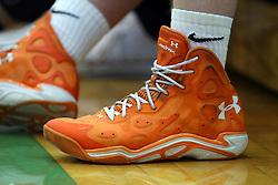 February 26, 2015: orange and white under armor basketball shoe with white nike socks