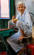 A senior in Saigon eats a mango in his pajamas. Robert Dodge, a Washington DC photographer and writer, has been working on his Vietnam 40 Years Later project since 2005. The project has taken him throughout Vietnam, including Hanoi, Ho Chi Minh City (Saigon), Nha Trang, Mue Nie, Phan Thiet, the Mekong, Sapa, Ninh Binh and the Perfume Pagoda. His images capture scenes and people from women in conical hats planting rice along the Red River in the north to men and women working in the floating markets on the Mekong River and its tributaries. Robert's project also captures the traditions of ancient Asia in the rural markets, Buddhist Monasteries and the celebrations around Tet, the Lunar New Year. Also to be found are images of the emerging modern Vietnam, such as young people eating and drinking and embracing the fashions and music of the West. His book. Vietnam 40 Years Later, was published March 2014 by Damiani Editore of Italy.