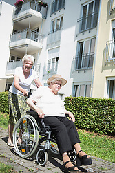 Senior woman pushing wheelchair of another woman at garden, Bavaria, Germany, Europe
