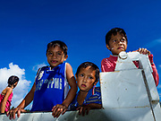 """22 JANUARY 2018 - CAMALIG, ALBAY, PHILIPPINES:  Boys in a government truck wait to be taken to an evacuation center. Their family had to leave their home on the slope of the Mayon volcano. There were a series of eruptions on the Mayon volcano near Legazpi Monday. The eruptions started Sunday night and continued through the day. At about midday the volcano sent a plume of ash and smoke towering over Camalig, the largest municipality near the volcano. The Philippine Institute of Volcanology and Seismology (PHIVOLCS) extended the six kilometer danger zone to eight kilometers and raised the alert level from three to four. This is the first time the alert level has been at four since 2009. A level four alert means a """"Hazardous Eruption is Imminent"""" and there is """"intense unrest"""" in the volcano. The Mayon volcano is the most active volcano in the Philippines. Sunday and Monday's eruptions caused ash falls in several communities but there were no known injuries.   PHOTO BY JACK KURTZ"""