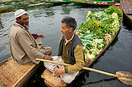 Two men talk on their boats. Floating vegetable market, Dal Lake.