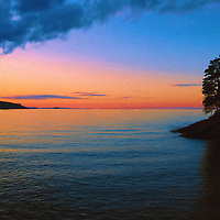 """""""Chasing Sunset Oil Painting""""<br /> <br /> Stunning oil painting of a sunset and silhouette. Beautiful trees in silhouette in the right foreground with gorgeous orange, and blue hues of Lake Superior at sunset."""