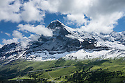 """The Eiger rises above Kleine Scheidegg pass, in the Berner Oberland, Switzerland, the Alps, Europe. The world's longest continuous rack and pinion railway (Wengernalpbahn) goes from Grindelwald up to Kleine Scheidegg and down to Wengen and Lauterbrunnen. From Kleine Scheidegg, Jungfraubahn ascends steeply inside the Eiger to Jungfraujoch, the highest railway station in Europe. UNESCO honors """"Swiss Alps Jungfrau-Aletsch"""" on the list of World Heritage Areas."""