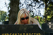 woman visits a grave at a Cemetery in Belgrade, Serbia